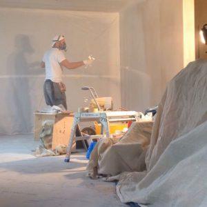 man applying mist coat onto new plaster